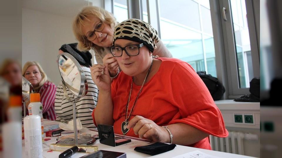 Kursleiterin Ellen Geißler gibt Pina G. Tipps beim Auftragen des Make-Ups. Wer gut aussieht, fühlt sich gleich besser, so die Idee der Veranstalter. (Foto: Lena Müssigmann)